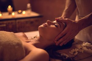 Young woman enjoying during head massage at the spa.